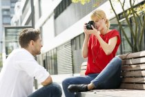 Woman taking a picture of her boyfriend with a camera — Stock Photo