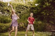 Mädchen und Jungen spielen mit Papier Flugzeuge im Garten — Stockfoto