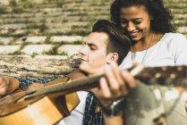 Coppie giovani rilassati con chitarra all aperto — Foto stock