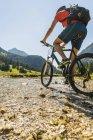 Австрия, Тироль, долина Танни, молодой человек на переправе на маунтинбайке — стоковое фото