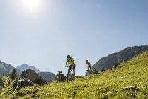 Autriche, Tyrol, vallée de Tannheim, jeune couple sur des vélos de montagne dans le paysage alpin — Photo de stock