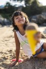 Little girl playing with sand on the beach — Stock Photo