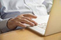 Senior man using a laptop — Stock Photo