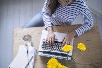 Mujer joven usando el ordenador portátil, trabajando desde casa - foto de stock
