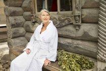 Donna maggiore sorridente in accappatoio seduti fuori Casetta sauna finlandese — Foto stock