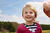 Ragazza bionda felice del bambino ritratto alzando in prato — Foto stock