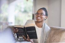 Портрет молодой женщины, сидящей на диване с книгой — стоковое фото