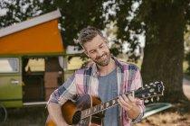 Smiling man in front of van playing guitar — Stock Photo