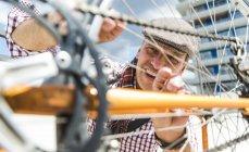 Reifer Mann repariert angelehntes Fahrrad — Stockfoto