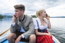 Germany, Bavaria, young couple wearing traditional clothes sitting in a rowing boat on Staffelsee — Stock Photo
