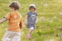 Toddler boy and girl catching soap bubbles on meadow — Stock Photo