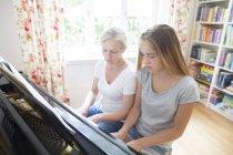 Madre e hija juntos tocando el piano - foto de stock