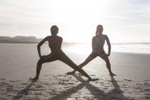 Две женщины, делать упражнения на растяжку на пляже в подсветки — стоковое фото