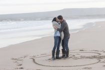 Young couple kissing on the beach — Stock Photo