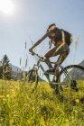 Молодая женщина на горном велосипеде в альпийском пейзаже — стоковое фото