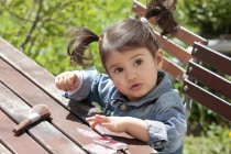 Портрет маленька дівчинка, що сидить на садовий стіл макіяж пензлем та rouge — Stock Photo