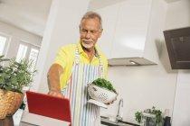 Человек с помощью цифрового планшета на кухне — стоковое фото