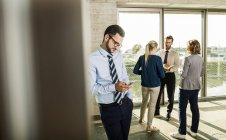 Businessman using smartphone with colleagues on background — Stock Photo