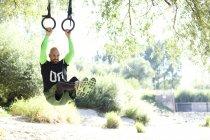 Человек делает кроссфит упражнения на кольцах висит на стволе дерева — стоковое фото