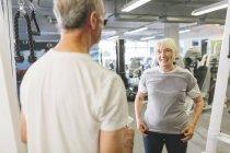 Senior mujer sonriendo a hombre en gimnasio - foto de stock