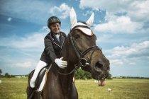 Улыбаясь всадник на коне на открытом воздухе — стоковое фото