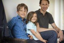Улыбаясь отец с сыном и дочерью, сидя у себя дома — стоковое фото