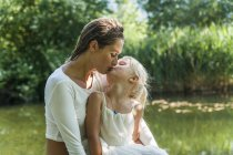 Mother and daughter kissing at a lake — Stock Photo