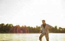 Homme de patauger dans l'eau d'une rivière au crépuscule du soir — Photo de stock