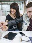 Giovani coppie che hanno divertimento alla caffetteria — Foto stock