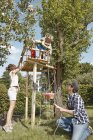 Family playing at tree house in garden — Stock Photo