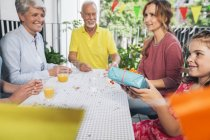 Granddaughter holding gift at family party — Stock Photo