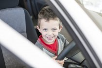 Happy boy at car dealer inside car steering — Stock Photo
