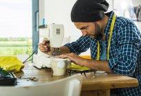 Junger Mann zu Hause mit Nähmaschine — Stockfoto