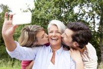 Glückliche Mutter mit erwachsenen Kindern, die Handy-Aufnahme im freien — Stockfoto