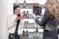 Mulher tirando foto com tablet digital na loja de sapatos — Fotografia de Stock