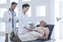 Senior bei Kontrolle im Krankenhaus, Krankenschwester beruhigt ihn — Stockfoto