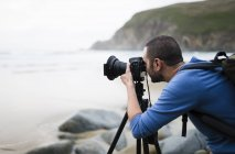 Spain, Valdovino, photographer on the beach with tripod and camera — Stock Photo