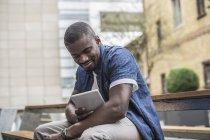 Homme assis sur un banc avec tablette numérique — Photo de stock