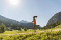 Austria, Tirol, Valle de Tannheim, joven trotar en el paisaje alpino - foto de stock