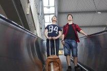Two teenage boys with baggage standing on an escalator — Stock Photo