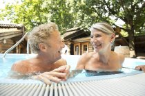 Happy senior couple in swimming pool at a spa — Stock Photo