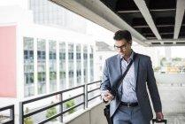 Geschäftsmann auf Geschäftsreise sein Smartphone betrachten — Stockfoto
