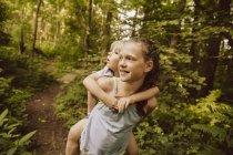 Girl carrying little boy piggyback through a forest — Stock Photo