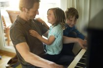 Father playing piano with daughter on lap and son — Stock Photo