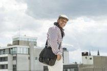 Зріла людина усміхнений носіння Кап ходьба в місті — стокове фото