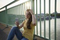 Femme avec smartphone assis sur le pont du Rhin — Photo de stock