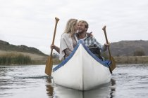 Happy young couple in a canoe on a lake — Stock Photo