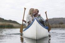Heureux jeune couple dans un canot sur un lac — Photo de stock