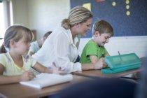Enseignant aide écolier dans la salle de classe à l'école — Photo de stock