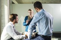 Three young business people discussing in office — Stock Photo